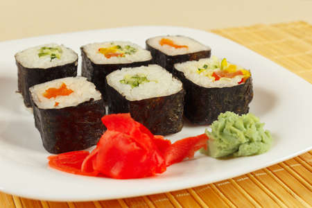 Sushi set with ginger and wasabi on a bamboo mat close up. Stock Photo