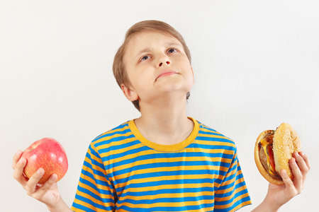Boy chooses between fastfood and healthy diet on a white background