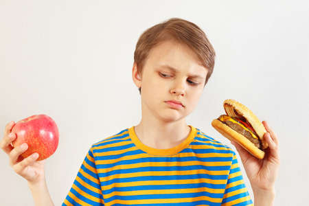 Boy chooses between hamburger and apple on a white background
