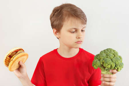 Boy chooses between hamburger and fresh broccoli on a white background Stock Photo