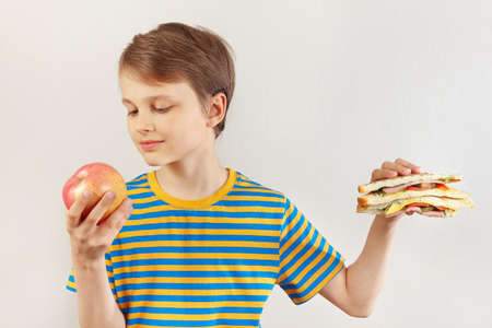 Boy chooses between sandwich and apple on a white background