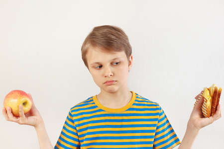 Young boy chooses between sandwich and healthy diet on a white background