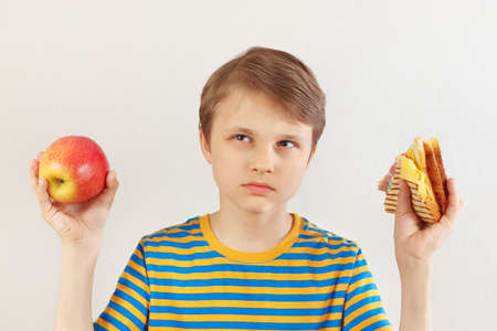 Little boy chooses between fastfood and healthy diet on a white background