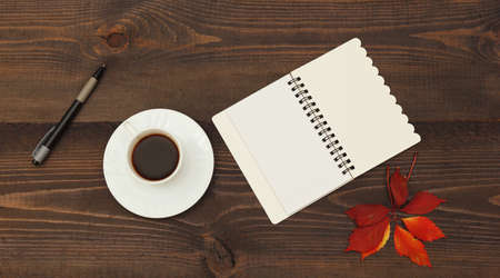 Cup of coffee, open notebook, pen and autumn red leaf on a wooden table. View from above. 免版税图像
