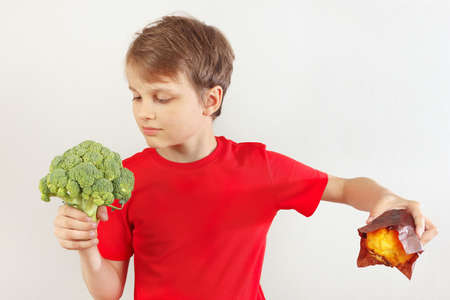 Boy chooses between fastfood and fresh vegetable on a white background
