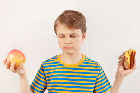 Boy chooses between sandwich and fresh apple on a white background
