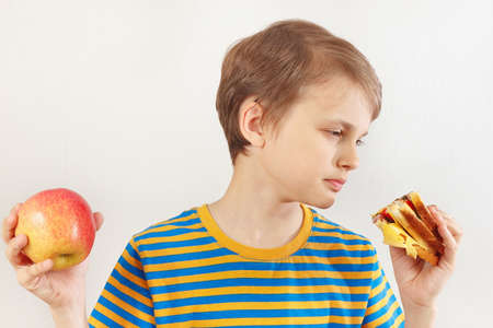 Young boy chooses between sandwich and fruit on a white background