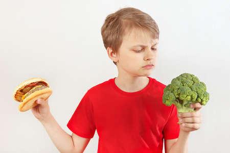 Chico elige entre comida rápida y brócoli sobre un fondo blanco. Foto de archivo