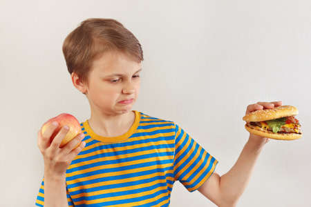 Young boy chooses between fastfood and healthy diet on a white background Stock Photo