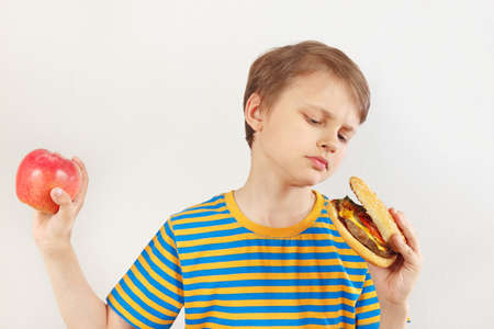 Young boy chooses between hamburger and apple on a white background