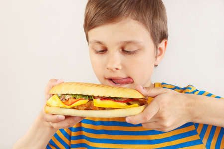 Young boy is licked at tasty cheeseburger on a white background