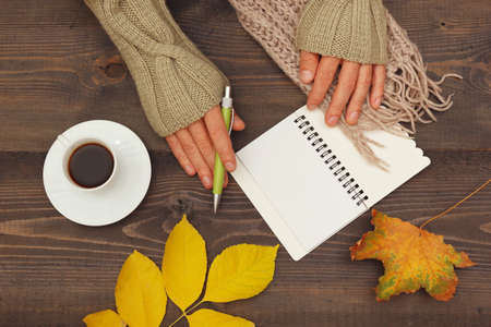 Hands of writer with a pen and notebook at a wooden table with a cup of espresso and autumn leaves and scarf