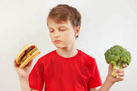 Boy chooses between fastfood and vegetable on a white background 스톡 콘텐츠 - 116683294