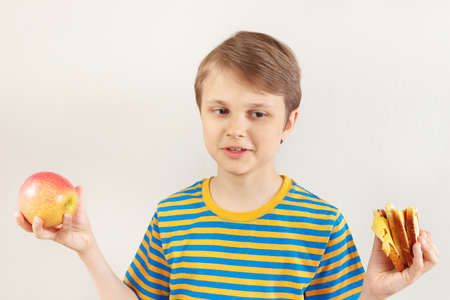 Boy chooses between sandwich and fresh fruit on a white background