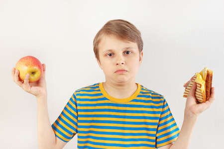 Young boy chooses between fastfood and fresh apple on a white background Stock Photo