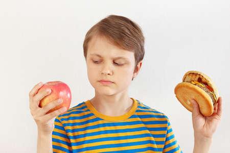 Chico elige entre hamburguesa y dieta saludable sobre un fondo blanco.