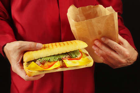 Hands of a man in a red k shirt take out a cheeseburger from a one-time package on a black background