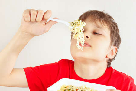 Little funny boy in a red shirt with instant noodles on a white background