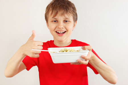 Young cut boy in a red shirt recommends instant noodles on a white background. Imagens - 120619961