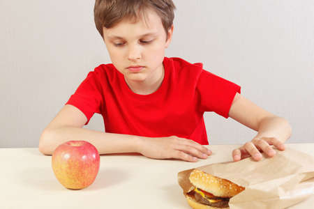 Boy at the table chooses between hamburger and healthy diet on a white background