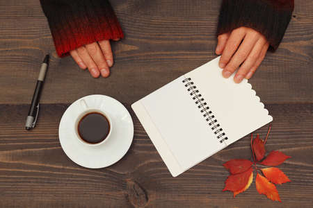 Hands of writer at a wooden table with a cup of espresso and a notebook with pen Stock Photo