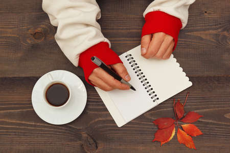 Human hands with a pen and notebook at a wooden table with a cup of espresso and autumn leaves 免版税图像