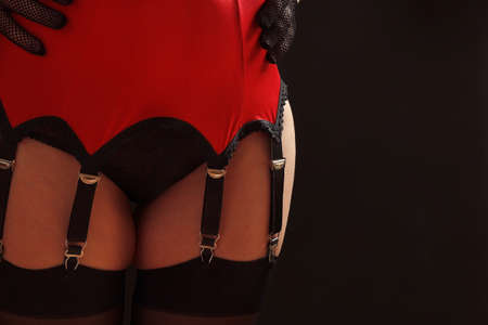 Sexy woman in stockings, garter belt and panties on a black background close up Reklamní fotografie - 120620180