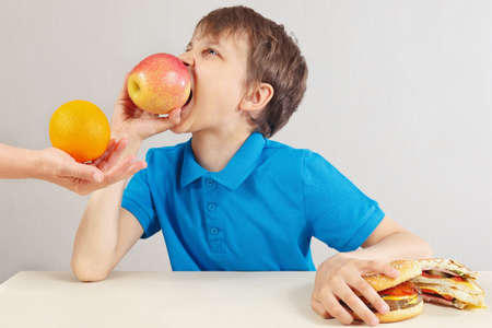 Little boy at the table chooses between fastfood and healthy diet on a white background
