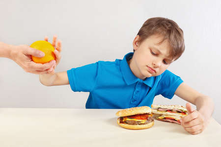 Young boy at the table chooses between fastfood and fruits on a white background Stock Photo