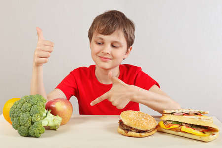 Young boy at the table chooses between fastfood and healthy diet on a white background 스톡 콘텐츠