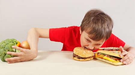 Young boy in red at the table chooses between fastfood and healthy diet on a white background