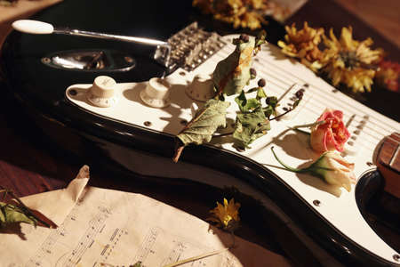 Electric guitar, dried flowers and old notes on wooden background close up.
