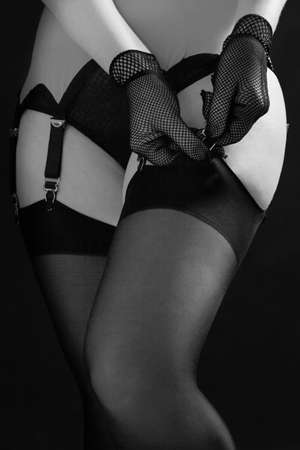 Woman fastens black stockings to the erotic garter belt on a black background close up. Fashion black and white photo.