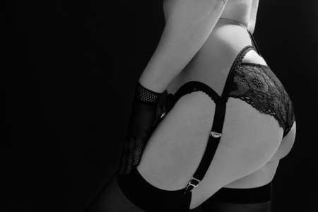 Woman in black stockings, garter belt and lace panties on a black background close up. Fashion black and white photo.