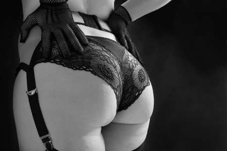 Beautiful woman in black stockings, erotic stocking belt and lace panties on a black background with smoke close up. Fashion black and white photo.