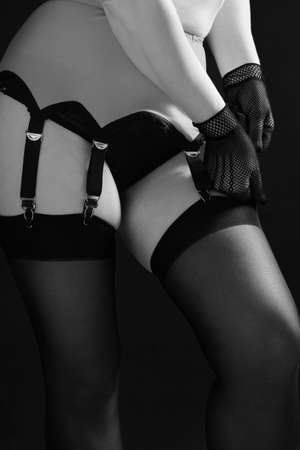 Sexy woman fastens stockings to the garter on a black background close up. Fashion black and white photo.