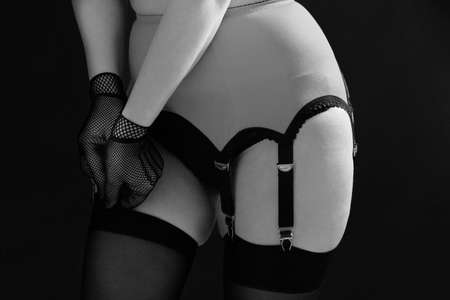 Woman fastens stockings to the erotic belt on a black background close up. Fashion black and white photo.