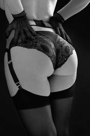 Beautiful woman in black stockings, stocking belt and lace panties on a black background close up. Fashion black and white photo. Reklamní fotografie