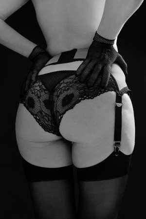 Beautiful woman in stockings, garter belt and lace panties on a black background close up. Fashion black and white photo.