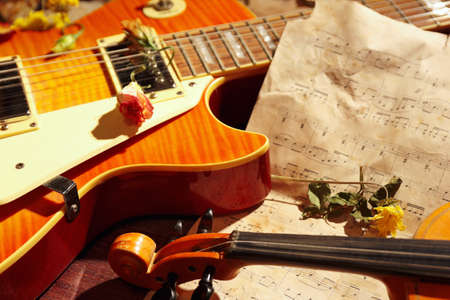 Vintage electric guitar, rare violin, dried flowers and old sheet music on wooden background close up. 版權商用圖片