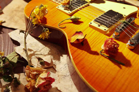 Vintage electric guitar, dried flowers and old notes on wooden background close up.