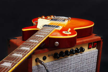 Brown guitar combo with honey sunburst guitar on the black background.