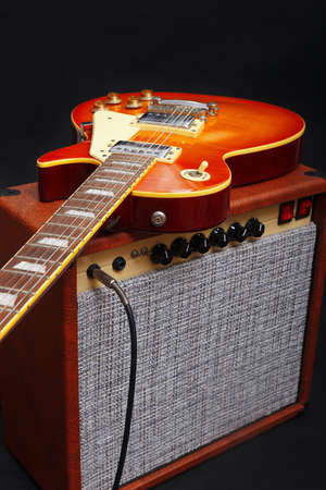 Brown tube combo amplifier for electric guitar with honey sunburst guitar on the black background.