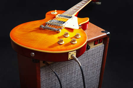Brown amplifier for guitar with honey sunburst guitar on the black background.