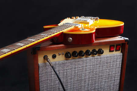 Guitar tube amplifier with honey sunburst guitar on the black background.