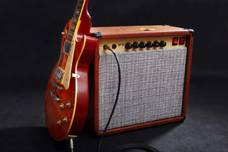 Tube combo amplifier for electric guitar with honey sunburst guitar on the black background.