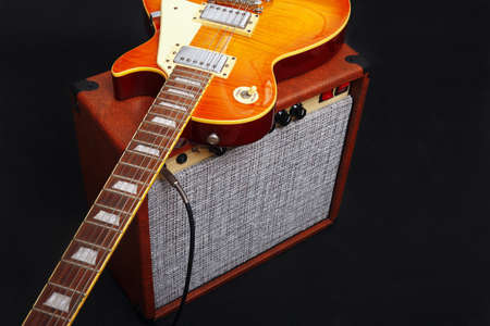 Brown tube combo amplifier for guitar with honey sunburst guitar on the black background.