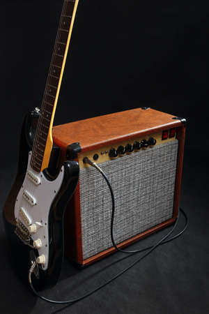 Combo amplifier for guitar with black guitar on the black background.