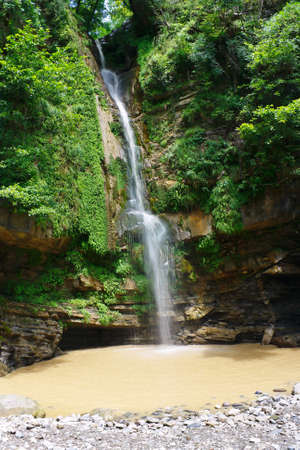 High marvelous waterfall falling from the rocks in a beautiful southern forest.