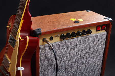Tube combo for electric guitar with honey sunburst guitar on the black background.
